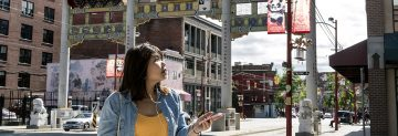 UBC alumna Ernielly Leo uses an augmented reality app to tour Vancouver's historic Chinatown neighbourhood. Developed by UBC professor Siobh‡n McPhee and students, the app is a historical walking tour that uses geolocation and audio files to enhance a user's experience. (Photo by Abigail Saxton)